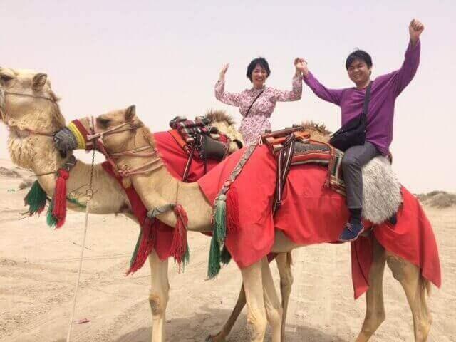 砂漠でラクダに乗った男女二人