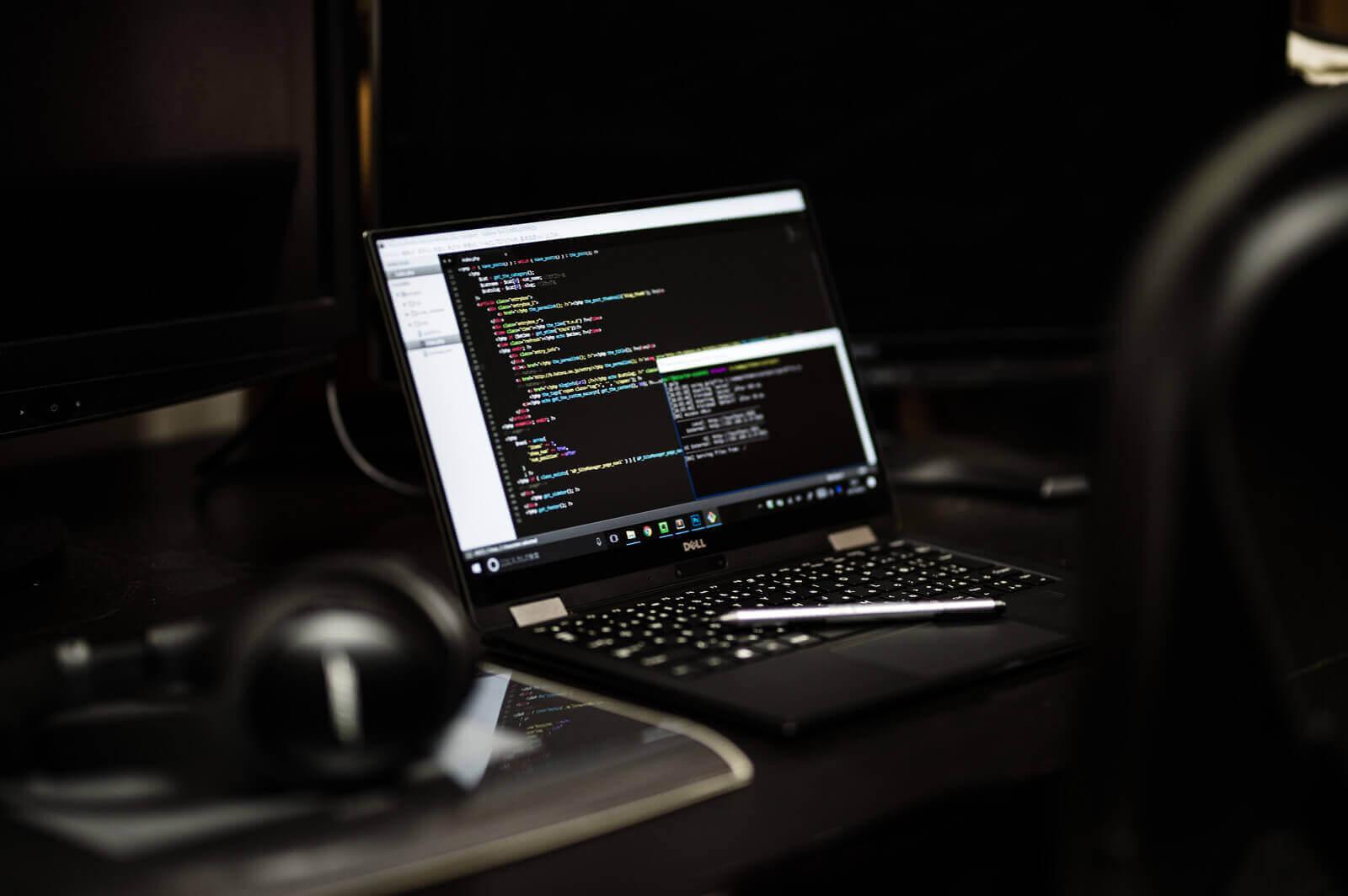 デスクに置かれたコーディング中のノートパソコンとヘッドホン